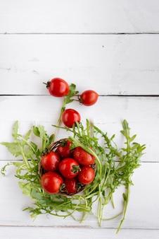 ルッコラムの天然産物の近くのテーブルの上に、サラダフロトプビューの赤いトマトの部品があります。ルッコラの葉は、木製のテーブルではなく、赤い完熟トマトの近くにあります。テキストの下に場所があります