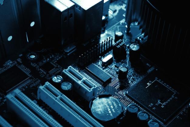 Компоненты на печатной плате чип, конденсатор вентилятора и разъемы на материнской плате компьютера