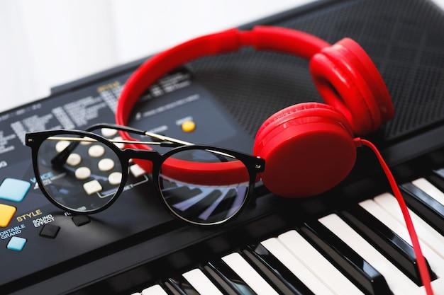 作曲または音楽鑑賞。シンセサイザーキーボードの赤いヘッドホンと眼鏡。