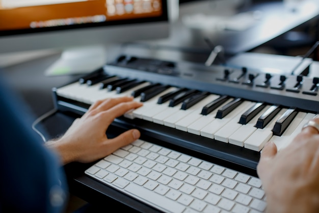 Composer hands on piano keys in recording studio. music production technology, man is working on pianino and computer keyboard on desk. close up concept.