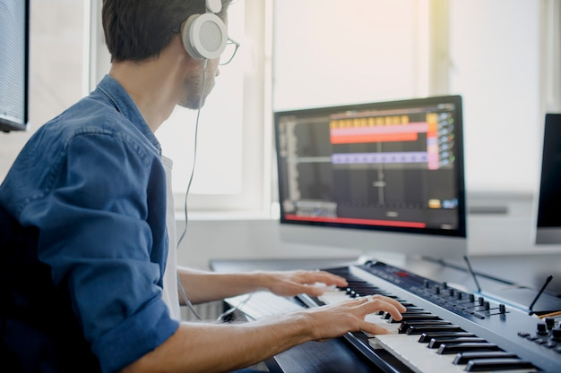 Composer hands on piano keys in recording studio. music production technology, man is working on pianino and computer keyboard on desk.