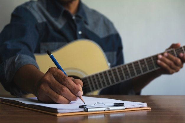 Composer holding pencil and writing lyrics in paper. musician playing acoustic guitar.