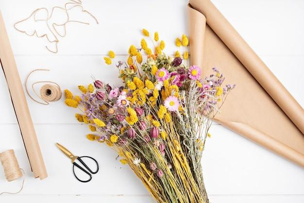 Составление букета из сухих цветов и трав, модное украшение интерьера, идея цветочного магазина кустарного промысла. вид сверху, плоская планировка