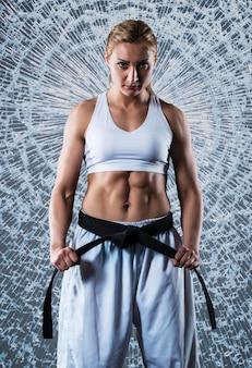 Composite image of karate girl wearing white sportswear and black belt, breaking glass in jump