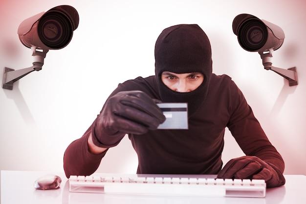 ノートパソコンとクレジットカードでオンラインショッピングをしている泥棒の合成画像
