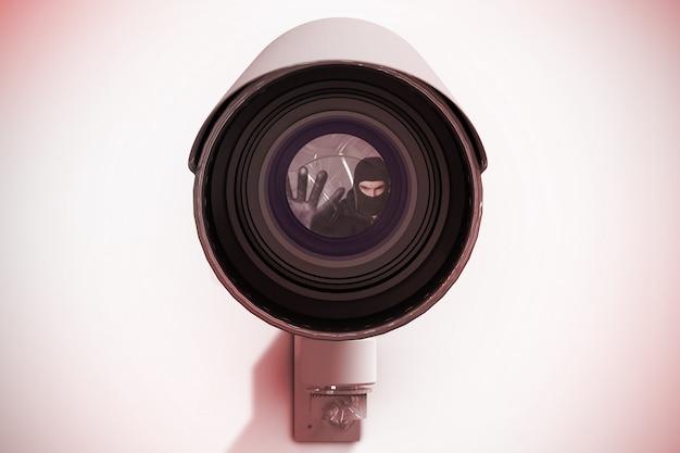 目出し帽を身振りでカメラを見ているハッカーの合成画像