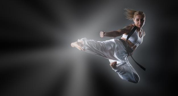 어두운 배경에서 점프하는 가라테 소녀의 합성 이미지