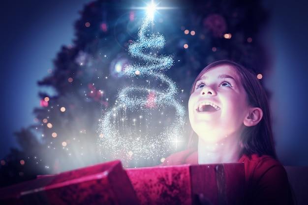 魔法のクリスマスプレゼントを開く少女の合成画像