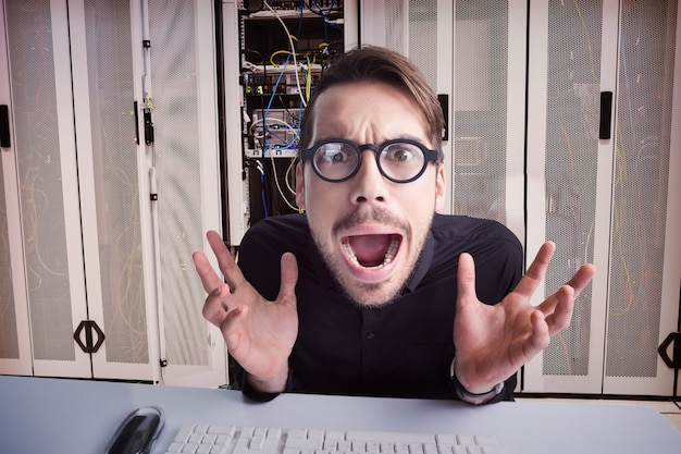 コンピューターを使用して眼鏡をかけて心配しているビジネスマンの合成画像