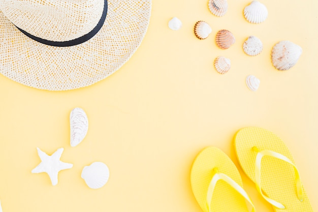Composition of accessories for exotic beach holiday on yellow background