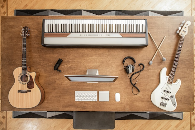 Composition of acoustic guitar, bass guitar, musical keys, a man at the computer and headphones and a shelf for drums on a large wooden table.