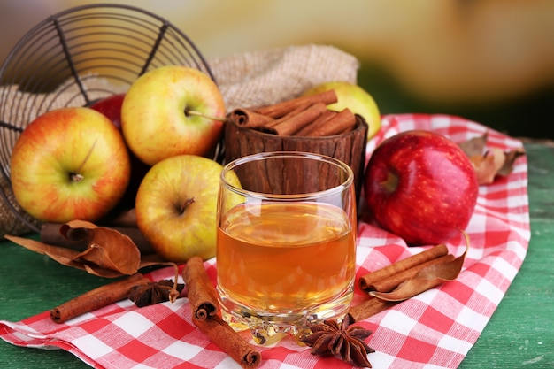 Composition of  apple cider in glass with cinnamon sticks, fresh apples and autumn leaves on wooden background