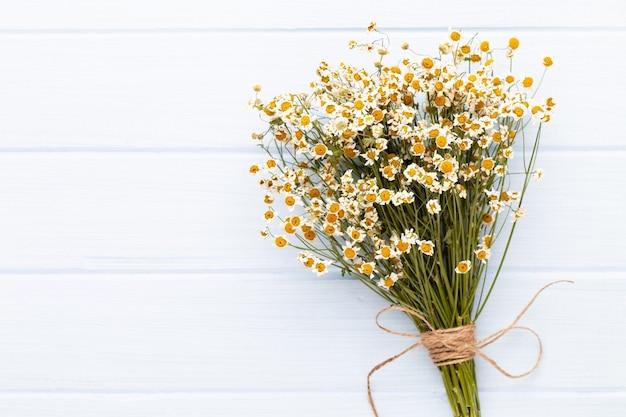 明るい背景に天然化粧品とカモミールの花を使ったコンポジションアロマテラピー。