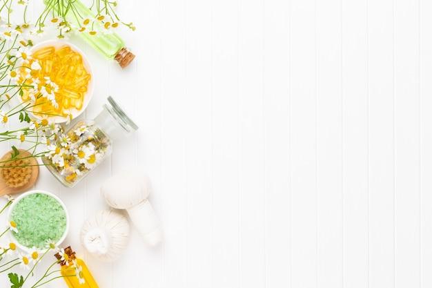 Композиция ароматерапии с натуральной косметикой и цветами ромашки на светлом фоне.