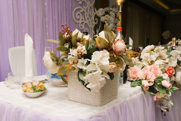 Composition of artificial flowers on the wedding table, banquet table decor in a restaurant