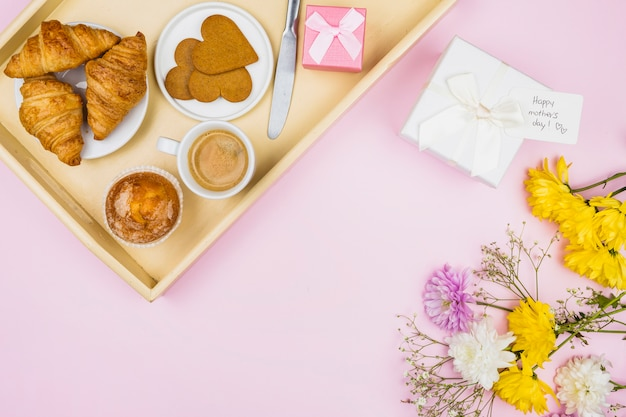 Composition of bakery and cup on tray near present and flowers