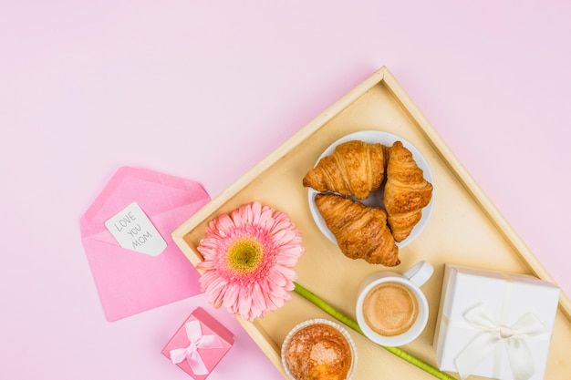 Composition of bakery, flower and present on tray near envelope with tag