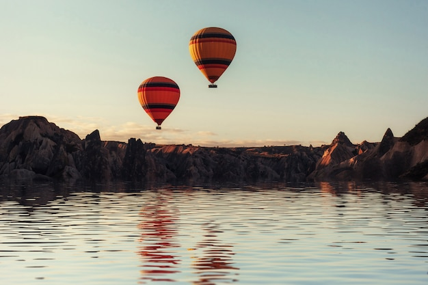 Composition of balloons over water and valleys