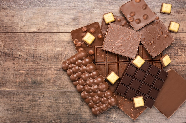素朴な木製の背景に、構成バーとさまざまなミルクとダーク チョコレートの部分。ミルクチョコレートの塊。トップ ビュー、コピー スペースでフレームを作るチョコレートの盛り合わせ