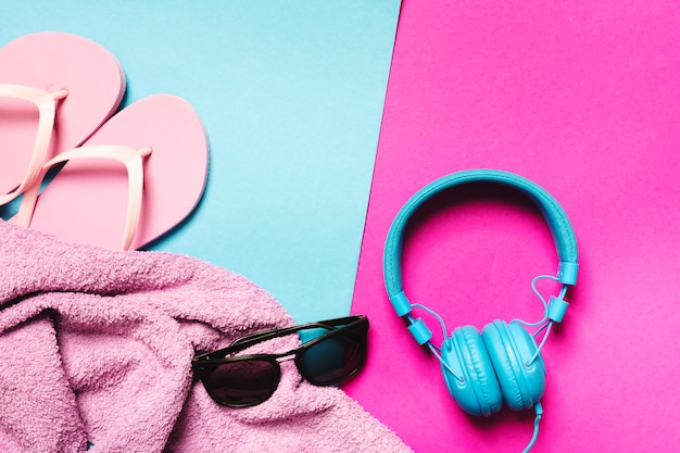 Composition of beach accessories and headphones on multicolored background
