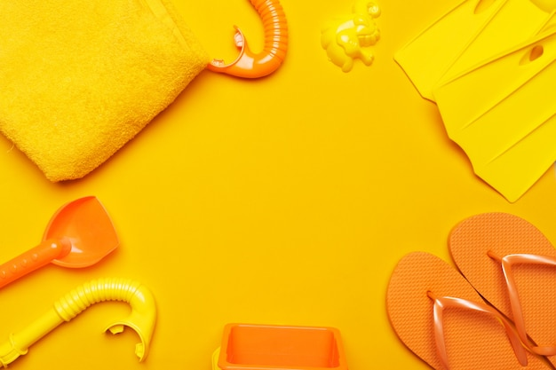 Composition of beachwear and accessories on a yellow background