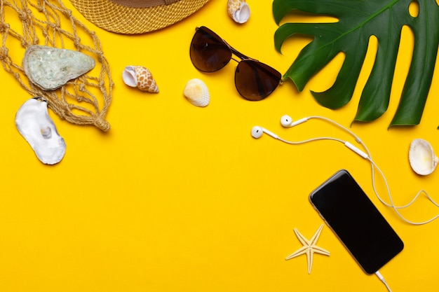 Composition of beachwear and accessories on yellow