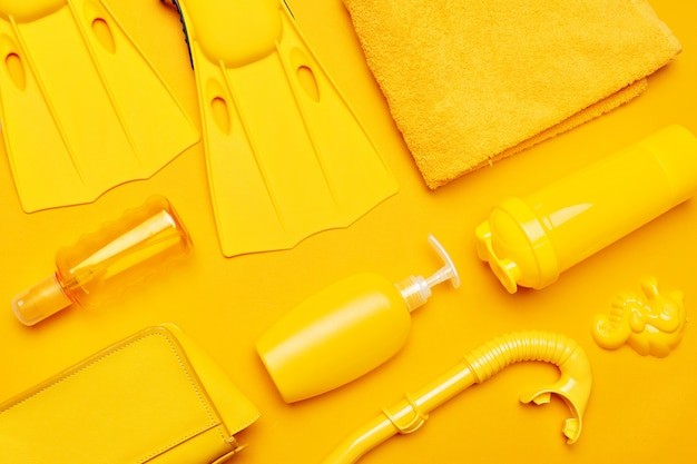 Composition of beachwear and accessories on a yellow