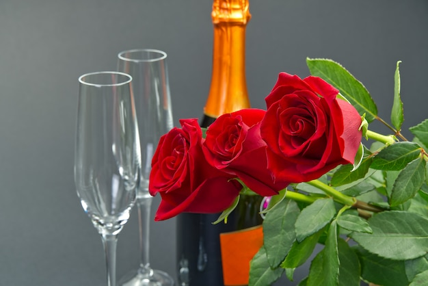 A composition of a beautiful bouquet of roses, glasses and a bottle of champagne creates a romantic card. the concept of st valentine's day, mother's day, march 8.