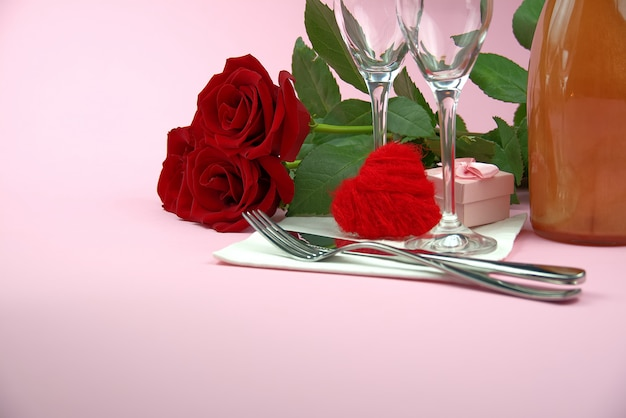 A composition of a beautiful bouquet of roses, glasses and a bottle of champagne creates a romantic card or poster. the concept of st valentine's day, mother's day, march 8.