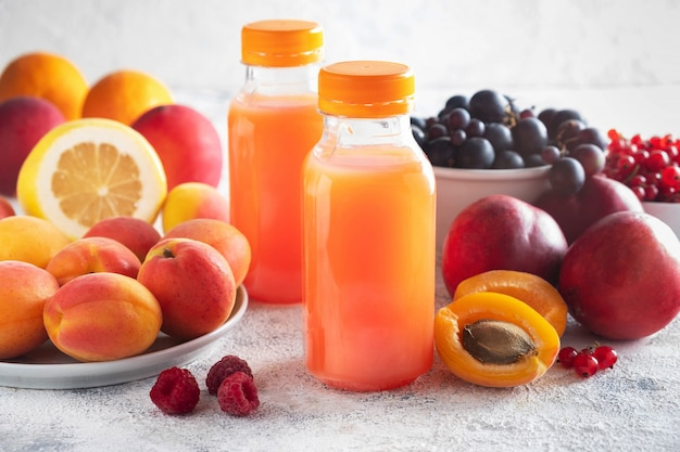 Composition of berries, fruits and bottled juice on a gray surface.