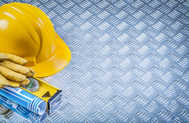 Composition of blue rolled blueprints building helmet safety gloves construction level on grooved metal background