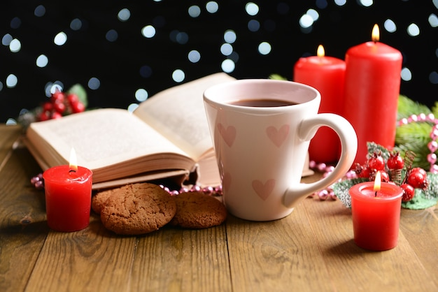 Composition of book with cup of coffee and christmas decorations on table on dark