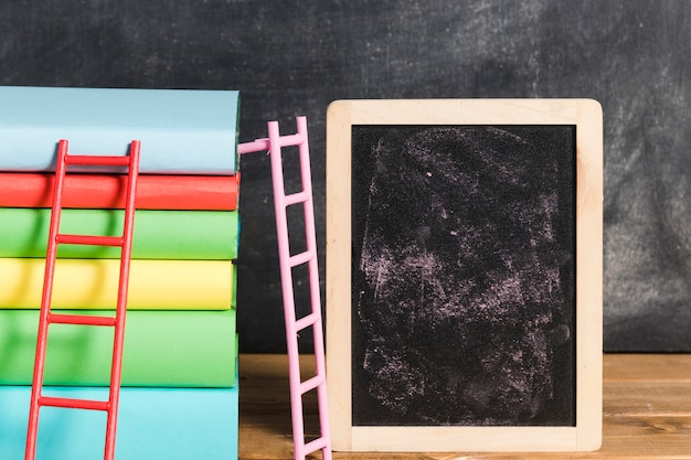 Composition of books with ladder near chalkboard