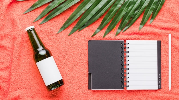 Composition of bottle notebook pen and green leaf
