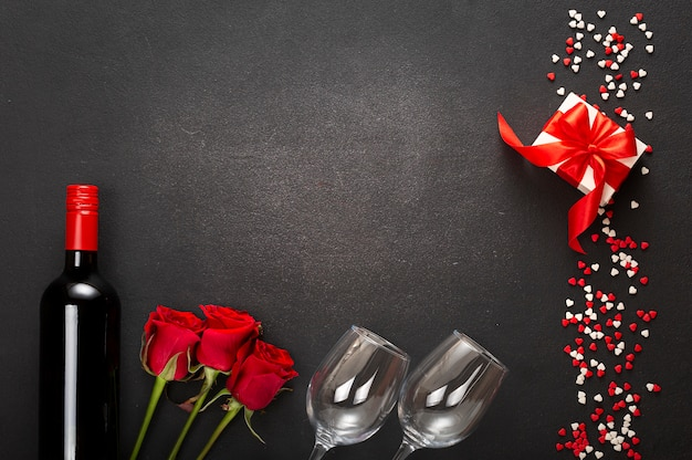 Composition of a bottle of wine, two glasses and a gift box with a red bow on a dark background. valentine's day, date, love.