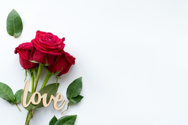 Composition of bouquet of red roses and decorative wooden word love on white background