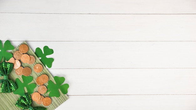 Composition of bow ties near coins and green paper clovers on board