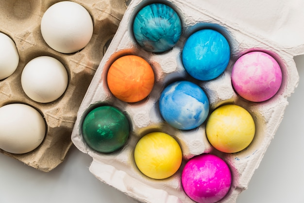 Composition of bright easter eggs in containers