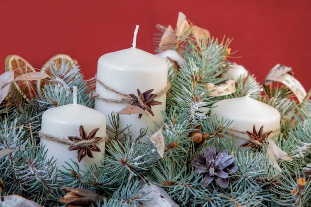 크리스마스를 위해 축제로 장식된 컴포지션 양초입니다. 아름다운 인사말 카드를 닫습니다.