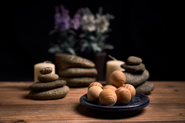 Composition of candles, stones and wooden spa balls on a wood and a black background