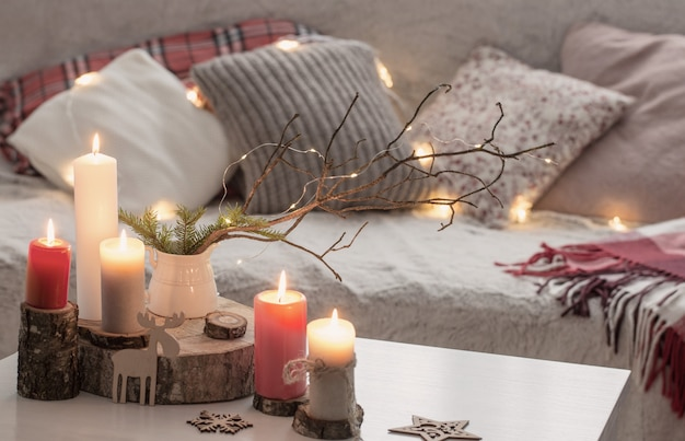 Composition of candles on white table near sofa with pillows