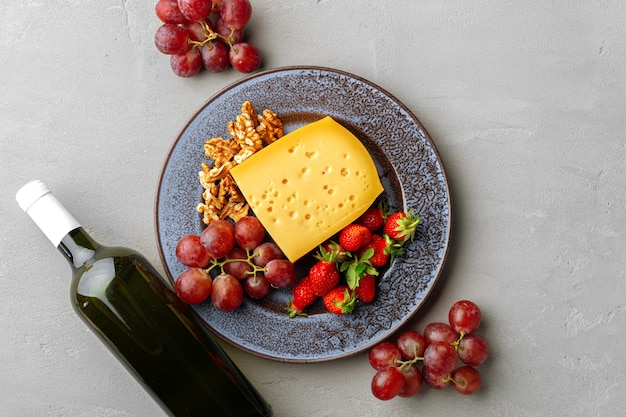 Composition of cheese, and fruits on gray table background