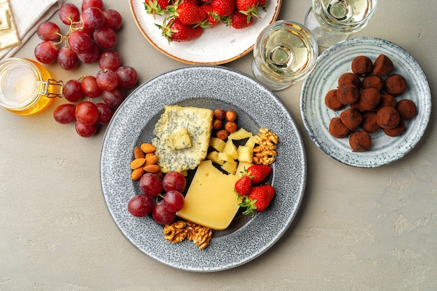 Composition of cheese, and fruits on gray table
