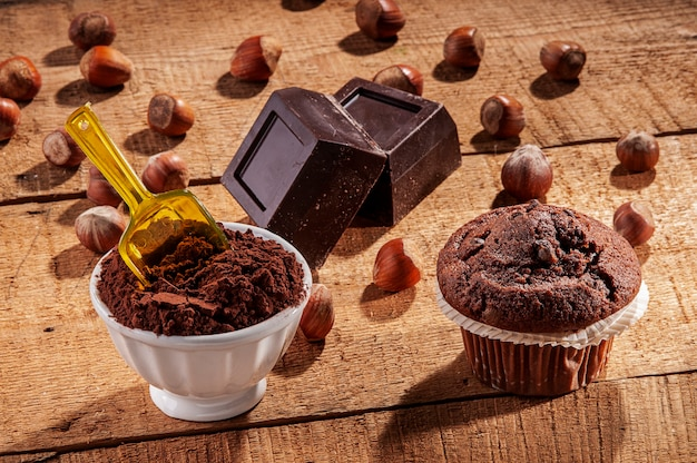 Composition of chocolate, cocoa and muffins on a wooden board