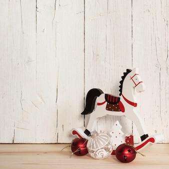 Composizione di addobbi natalizi e cavallo di legno con copia spazio