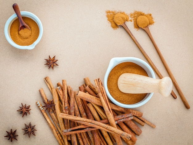 Composition of cinnamon stick and cinnamon powder on brown background .