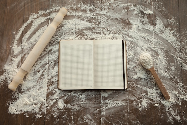 Composition of clear open recipe book in middle and rolling pin with spoon by sides on floured table.