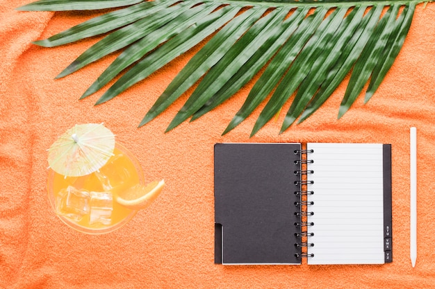Composition of cocktail notebook pen and leaf