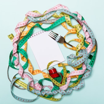 Composition of colorful measuring tapes, fork and notepad on blue