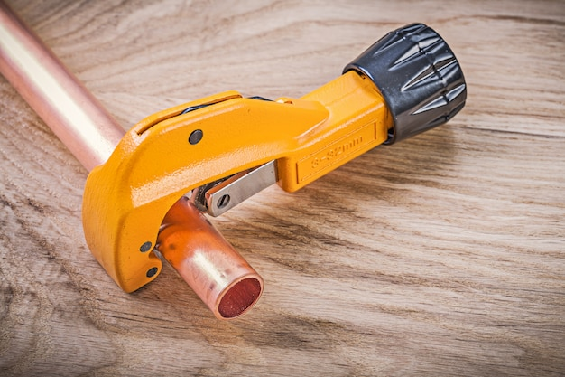 Composition of copper water pipe cutter on wooden board plumbing brassware concept